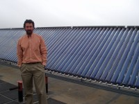 Professor Andrea Mammoli and solar collectors on the UNM Mechanical Engineering Building